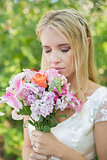 Blonde bride smelling her colourful bouquet