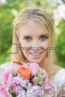 Blonde bride smiling at camera holding bouquet