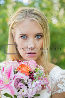 Blonde bride looking at camera holding bouquet