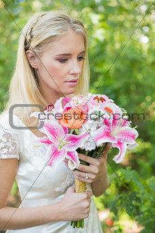 Calm bride holding her bouquet close