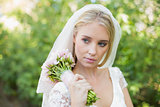 Peaceful bride holding her bouquet wearing a veil