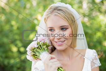Smiling bride holding her bouquet wearing a veil
