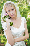 Pretty bride holding her bouquet wearing a veil