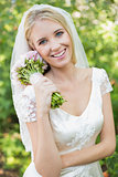 Pretty smiling bride holding her bouquet wearing a veil