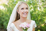 Pretty smiling bride holding her bouquet wearing a veil looking up
