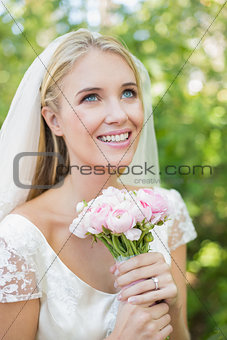 Smiling bride holding her bouquet wearing a veil looking up