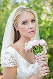 Peaceful bride holding her bouquet wearing a veil looking at camera