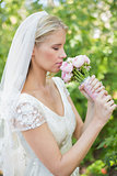 Peaceful bride smelling her bouquet