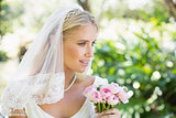 Happy bride in a veil holding her bouquet