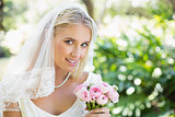 Happy bride in a veil holding her bouquet looking at camera