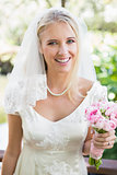 Smiling bride in a veil holding her bouquet looking at camera