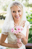Happy bride in a veil holding her rose bouquet