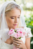 Happy bride in a veil smelling her rose bouquet