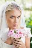 Blonde bride in a veil holding her rose bouquet