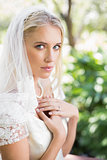 Blonde bride in a veil holding her hands to her chest