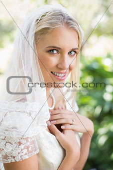 Blonde smiling bride in a veil holding her hands to her chest