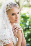 Smiling bride in a veil holding her hands to her chest