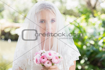 Smiling bride wearing veil over face holding rose bouquet