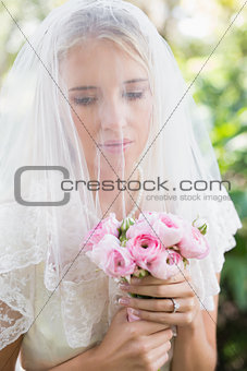 Calm bride wearing veil over face holding rose bouquet