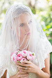 Content bride wearing veil over face holding rose bouquet