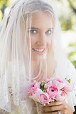 Smiling bride wearing veil over face holding bouquet looking at camera