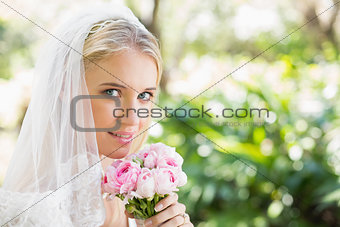 Smiling bride wearing veil holding bouquet looking at camera