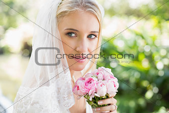 Smiling bride wearing veil holding bouquet