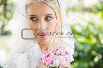 Smiling bride wearing veil holding bouquet looking over her shoulder