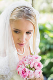 Smiling bride wearing veil holding bouquet looking down