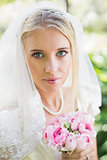 Happy bride wearing veil holding bouquet looking at camera