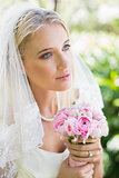 Content bride wearing veil holding bouquet looking away