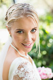 Blonde bride in a veil smiling to camera