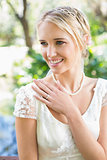 Happy blonde bride with hand on chest