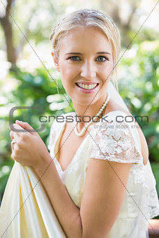 Smiling blonde bride holding her dress looking at camera