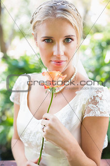 Smiling blonde bride in pearl necklace holding rose