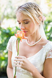 Smiling blonde bride in pearl necklace smelling rose