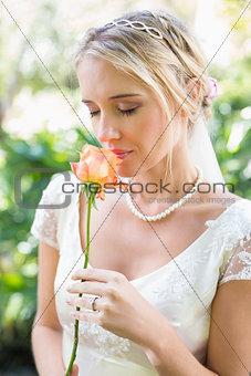 Smiling blonde bride in pearl necklace smelling rose