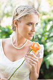 Smiling blonde bride in pearl necklace holding orange rose