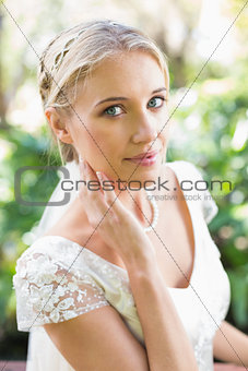 Smiling blonde bride in pearl necklace touching her face