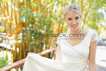 Smiling blonde bride in pearl necklace looking at camera