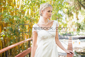 Smiling blonde bride in pearl necklace standing on a bridge