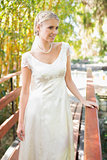 Happy blonde bride in pearl necklace standing on a bridge