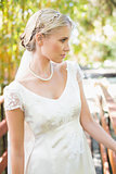 Calm blonde bride in pearl necklace standing on a bridge