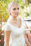 Pretty blonde bride in pearl necklace standing on a bridge