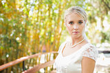 Pretty bride in pearl necklace standing on a bridge