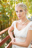 Pretty blonde bride standing on a bridge