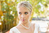 Pretty blonde bride standing on a bridge looking away