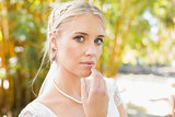 Pretty blonde bride standing on a bridge looking at camera