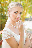 Pretty smiling blonde bride standing on a bridge looking at camera