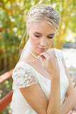 Pretty smiling blonde bride standing on a bridge looking down
